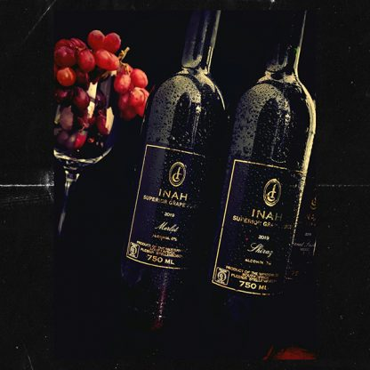 The Red Vintage Merlot and Shiraz Inah Superior Grape Juice Bottles next ti a wine glass filled with fresh red grapes