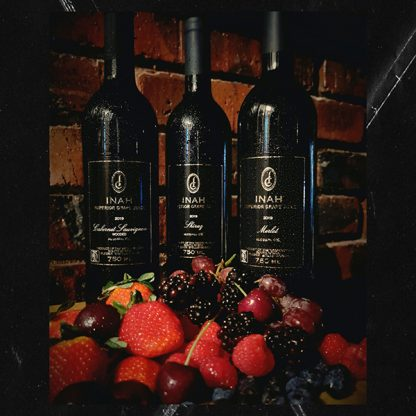 The Red Vintage Cabernet Sauvignon, Mrlot and Shiraz Inah Superior Grape Juie Bottles, against a brick wall and behind a succulent display of Fresh Berries