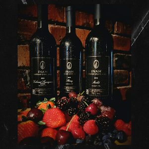 Cabernet Sauvignon, Merlot and Shiraz Inah Superior Grape Juie Bottles, against a brick wall and behind a succulent display of Fresh Berries