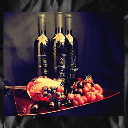 The Red Vintage Cabernet Sauvignon, Merlot and Shiraz Inah Superior Grape Juie Bottles, against a brick wall and behind a succulent display of Fresh red Grapes on a gold Platter