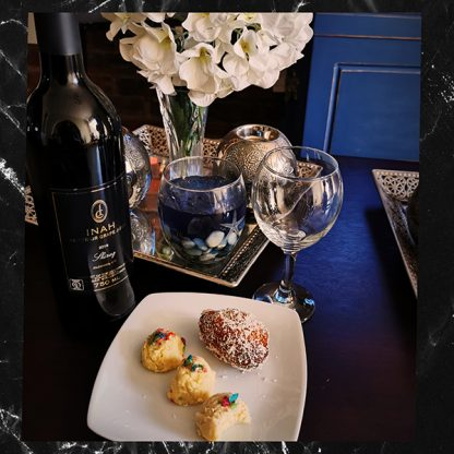The Red Vintage Shiraz Inah Superior Grape Juice displayed with a plate of desserts and a tumbler filled with the grape juice