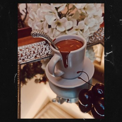 Belcolade Belgian Chocolate melted in an espresso cup displayed on a saucer and a mirror with White Flowers