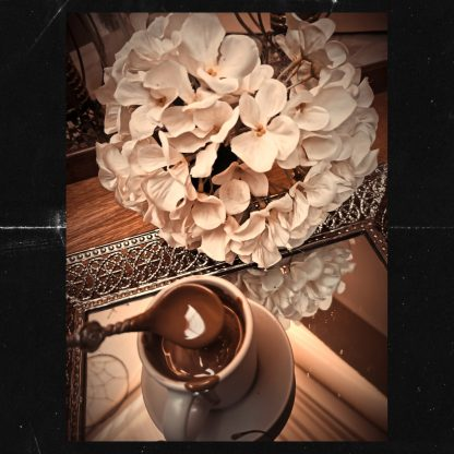 The Red Vintage Belcolade Belgian Chocolate melted in an espresso cup displayed on a saucer and a mirror with White Flowers captured from the top