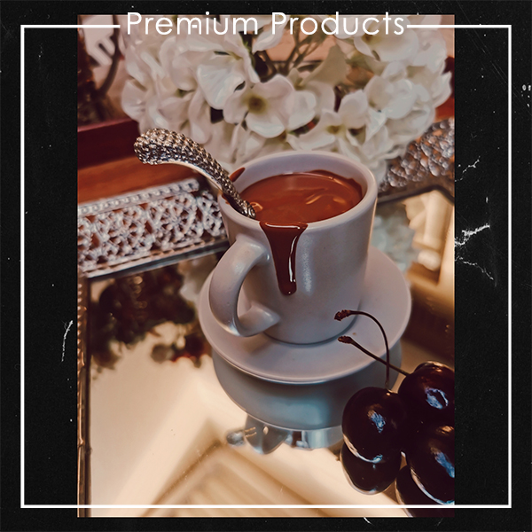 The Red Vintage Belcolade Belgian Chocolate melted in an espresso cup displayed on a saucer and a mirror with White Flowers