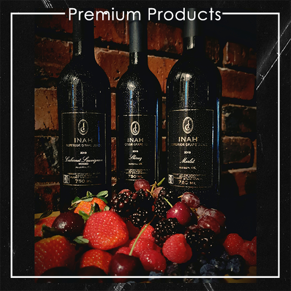 The Red Vintage Cabernet Sauvignon, Merlot and Shiraz Inah Superior Grape Juie Bottles, against a brick wall and behind a succulent display of Fresh Berries