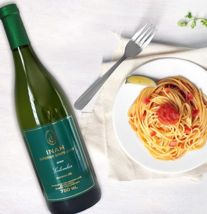 The Red Vintage - INAH Colombar 100% Grape Juice Bottle lying on a table next to a appetizing spaghetti meal